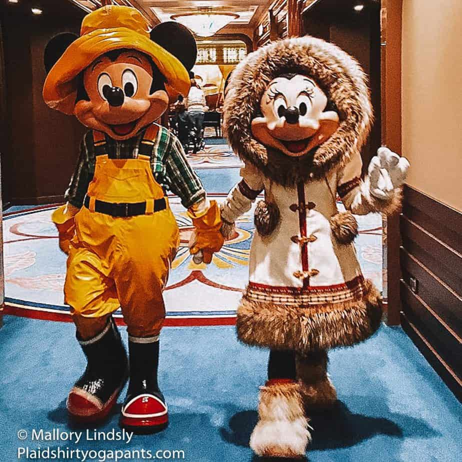 Minnie and Mickey walking hand in hand in their iconic Alaskan gear on the Disney Wonder.